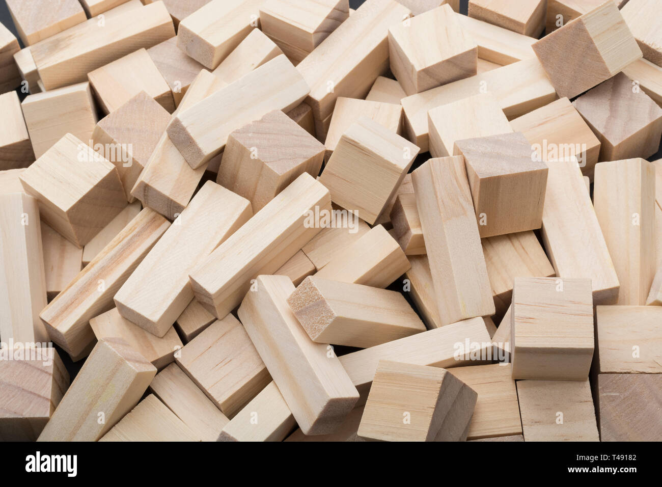 Small wooden bricks scattered in a disorganised pile. Metaphor chaos, messy, untidy, jumbled up, mixed up, in a muddle, confused thoughts, tumble. - Stock Image