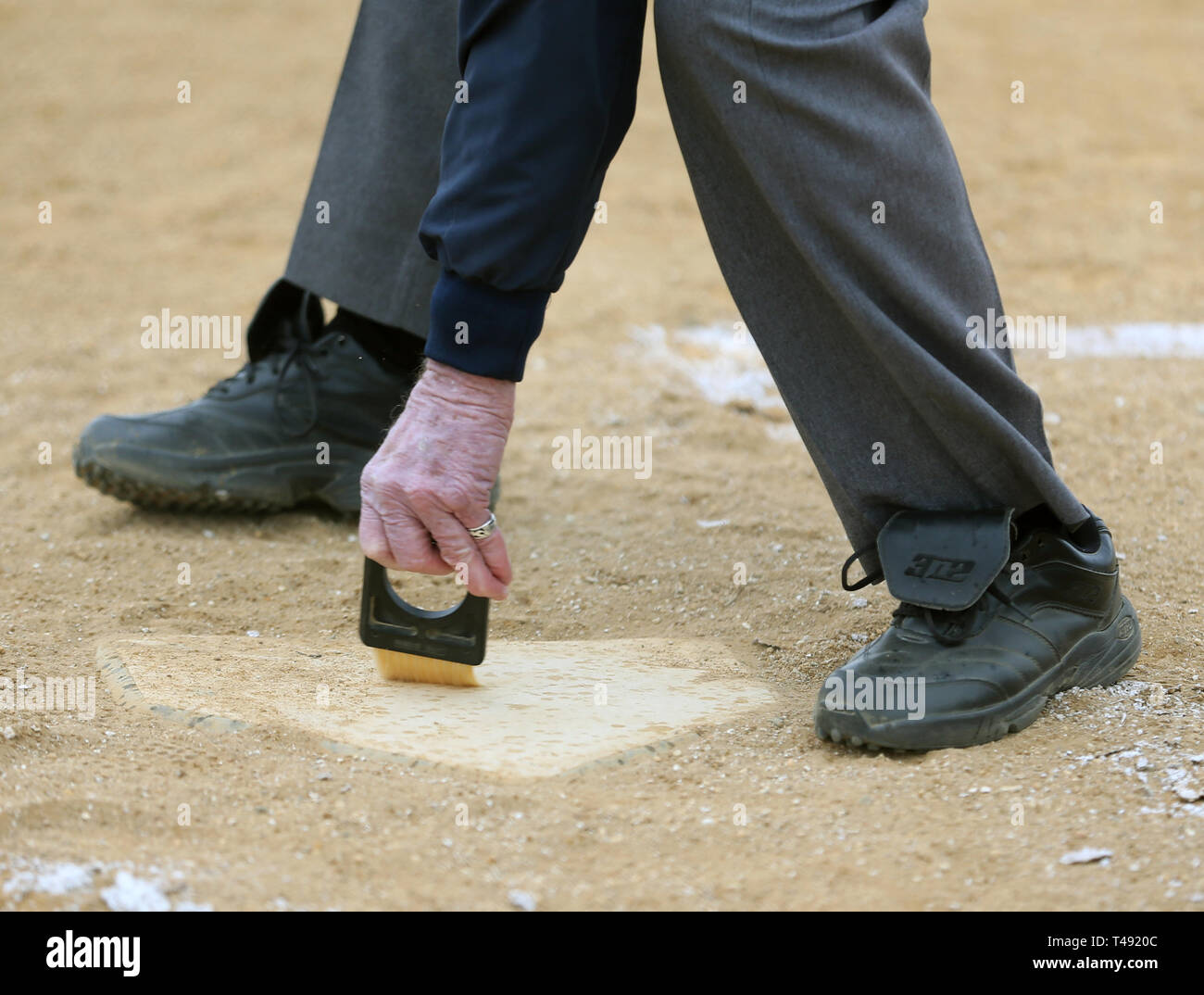 Umpire cleaning home plate at a baseball game Stock Photo