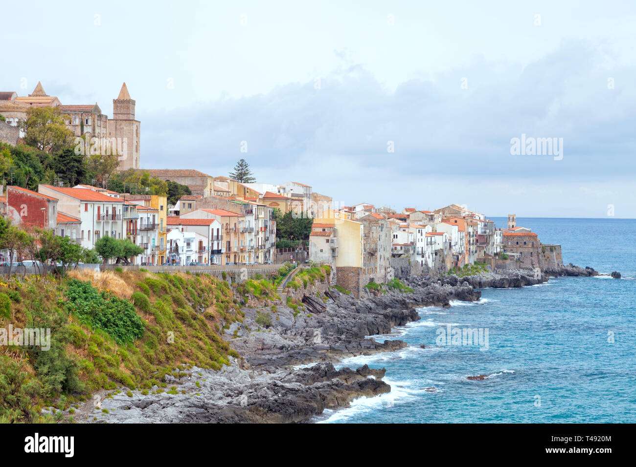 Rocky coast of Sicilian seaside resort of Cefalu with historic houses, cathedral on the hill, promenade . - Stock Image