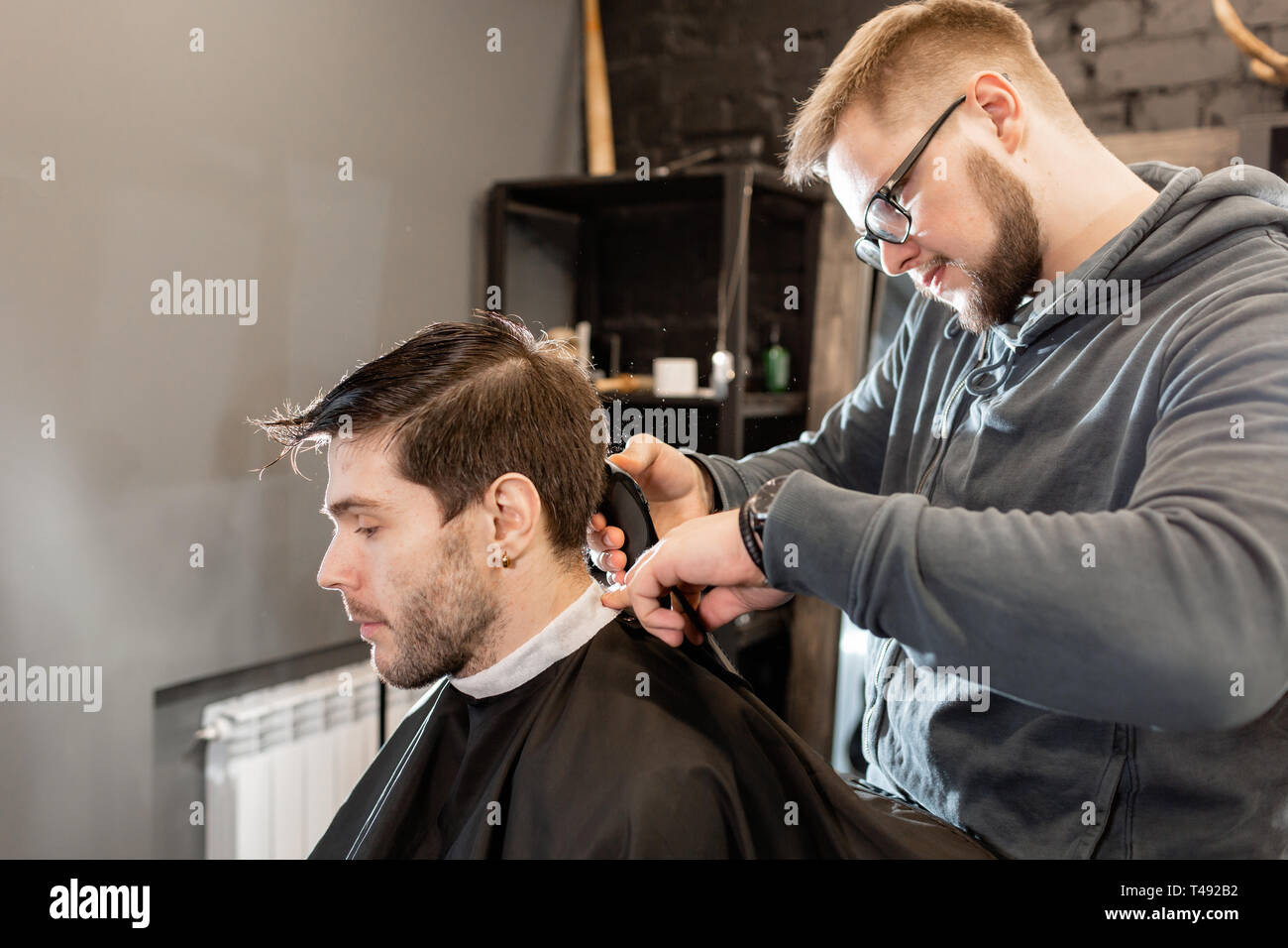 Barber work with clipper machine in barbershop. Professional trimmer tool cuts beard and hair on young guy in barber shop salon. Stock Photo