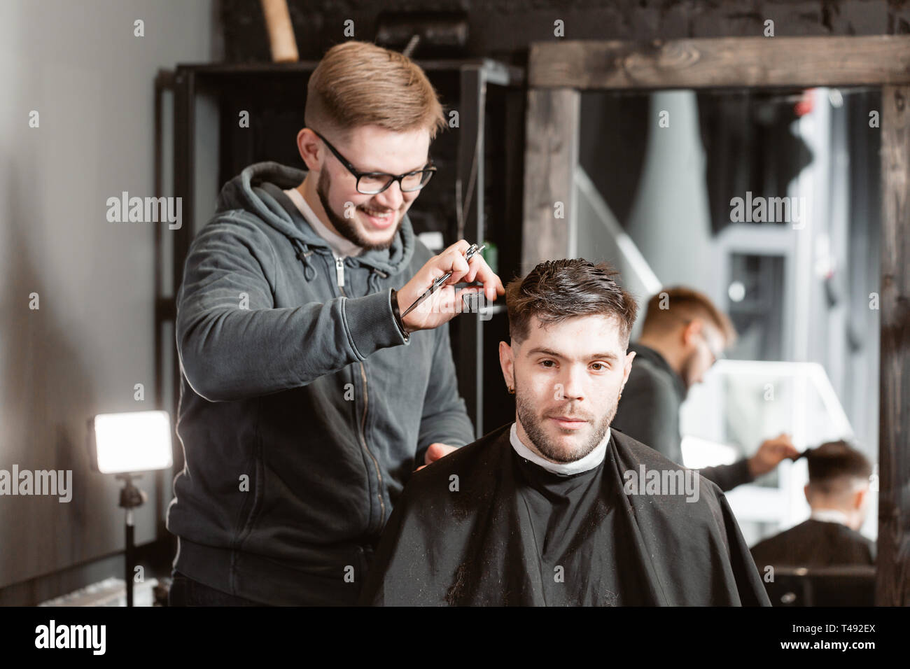 Hair cutting with metal scissors. Master cuts hair and beard