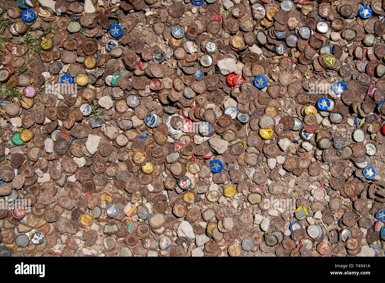 Beer bottles caps covering the backyard of a bar in Marfa, Texas. - Stock Image