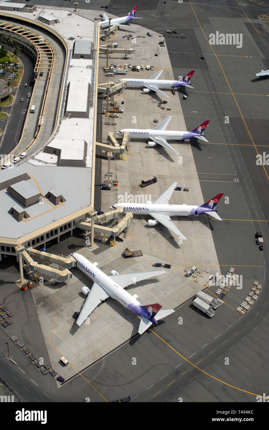 A portrait aerial view of jet airliners at the gates at a major airport in Hawaii. - Stock Image