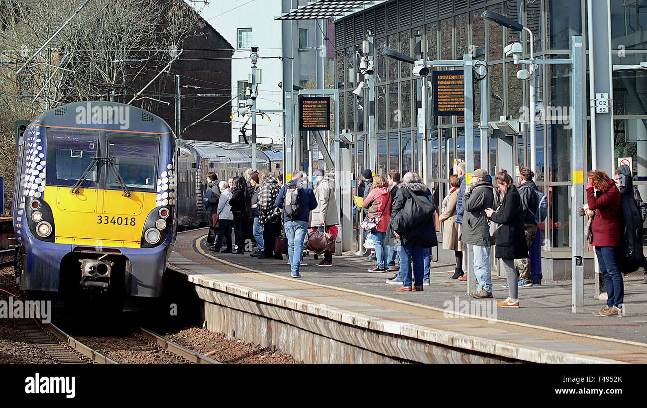Train with commuters or passengers at Partick railway station, Glasgow, Scotland, UK - Stock Image