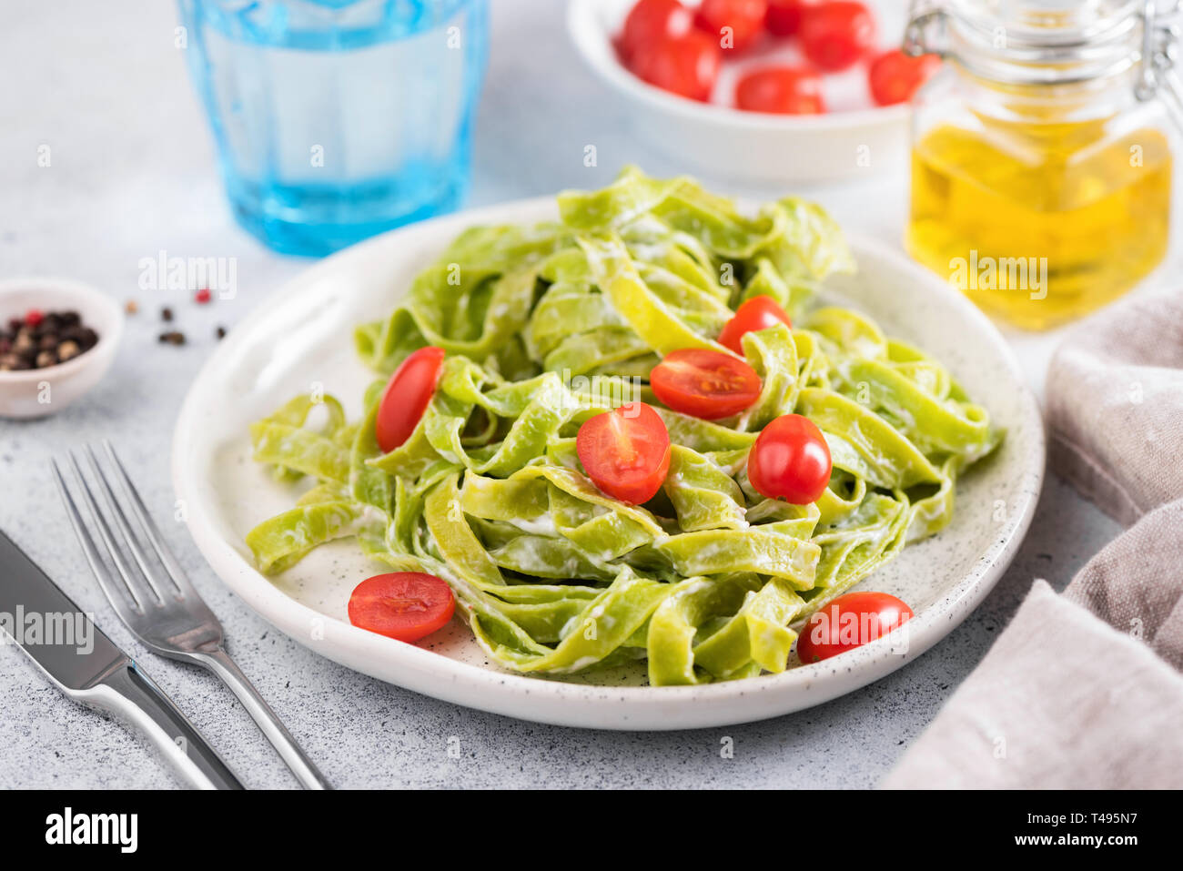 Green spinach pasta with cream sauce and tomatoes on a plate. Italian cuisine food. Closeup view, horizontal orientation - Stock Image