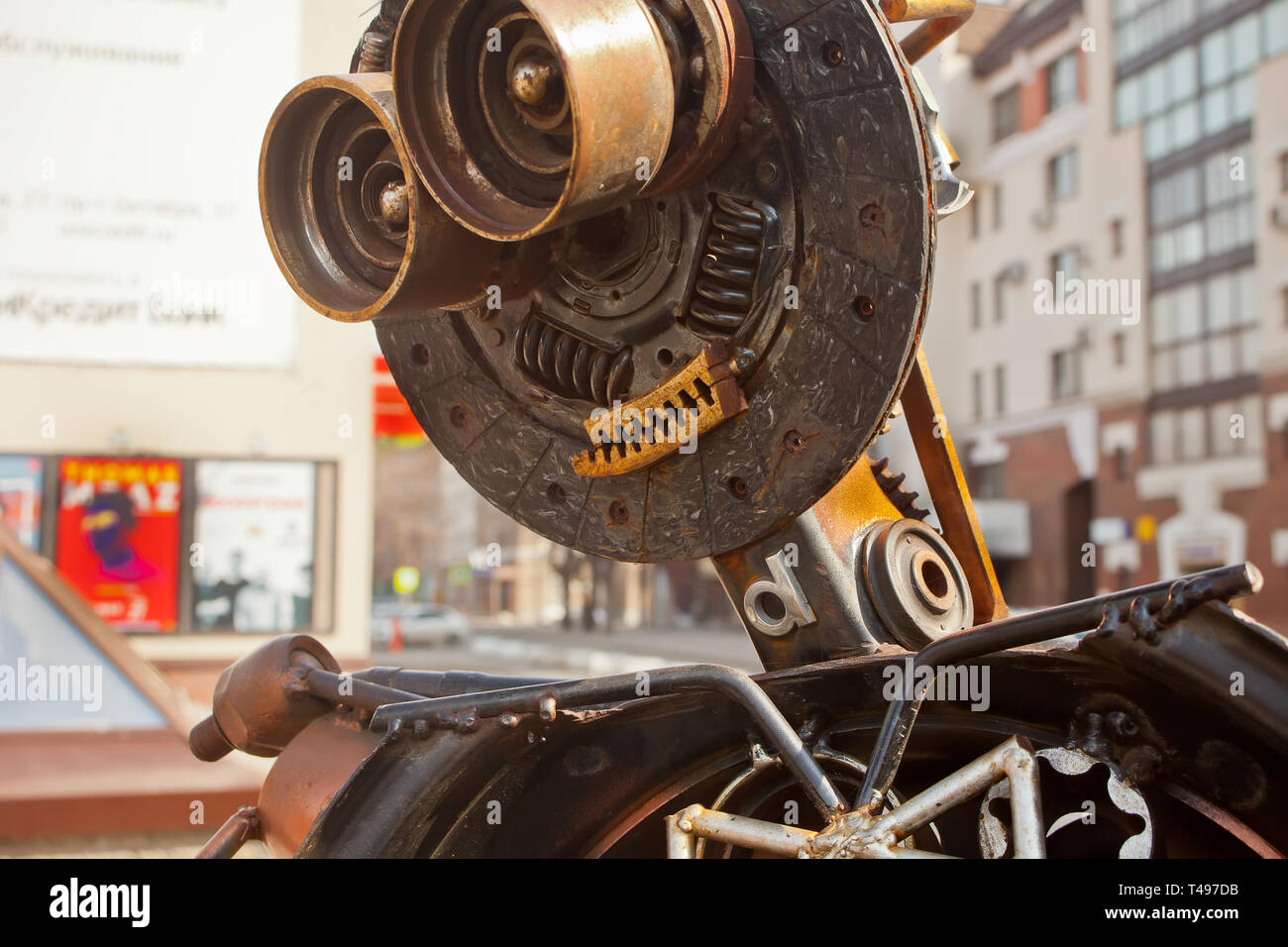 Metal sculpture of trash compactor robot made of rusty details of old cars. Close up head of robot. Selective focus Stock Photo