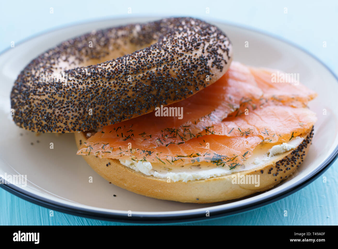 Poppy seeds bagel with cream cheese and smoked salmon served on a