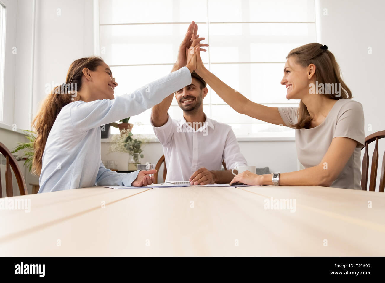 Three partners business team people give high five together Stock Photo
