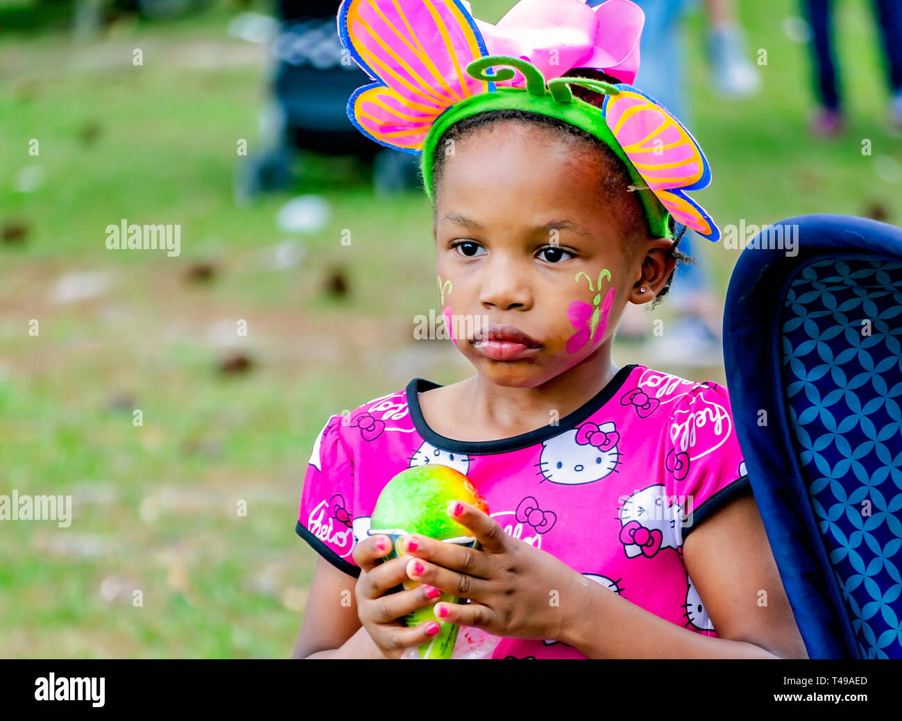 A girl in bunny ears holds a rainbow-colored sno-cone during a community Easter egg hunt at Langan Park, April 13, 2019, in Mobile, Alabama. - Stock Image