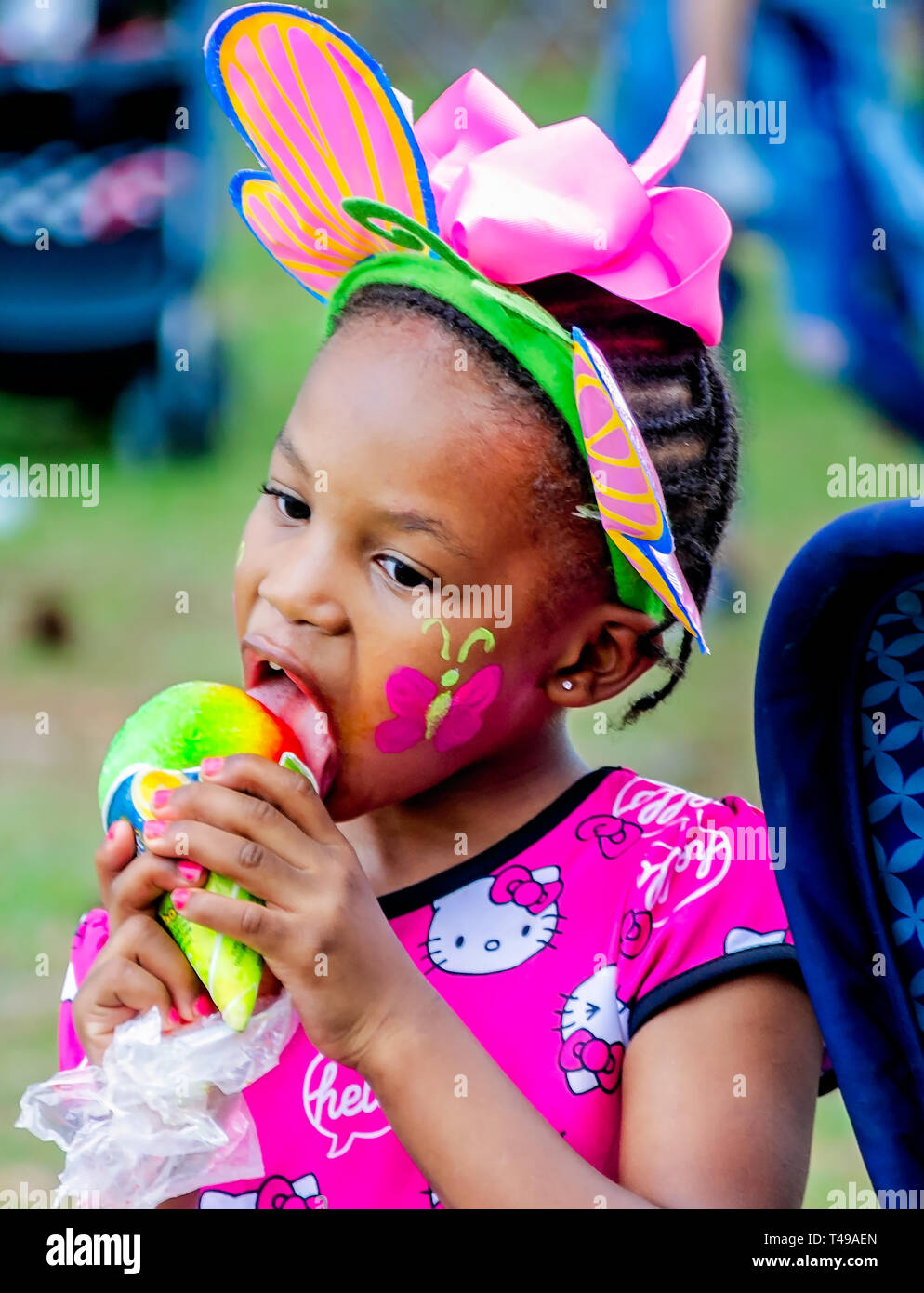 A girl in bunny ears eats a rainbow-colored sno-cone during a community Easter egg hunt at Langan Park, April 13, 2019, in Mobile, Alabama. - Stock Image