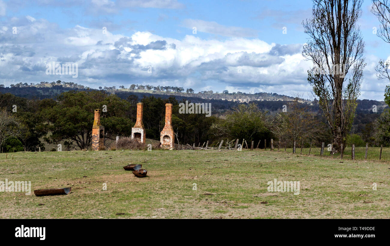 Ruins of three chimneys and fire places reminders of a glorious bygone era in the rural countryside of New England, in New South Wales, Australia - Stock Image