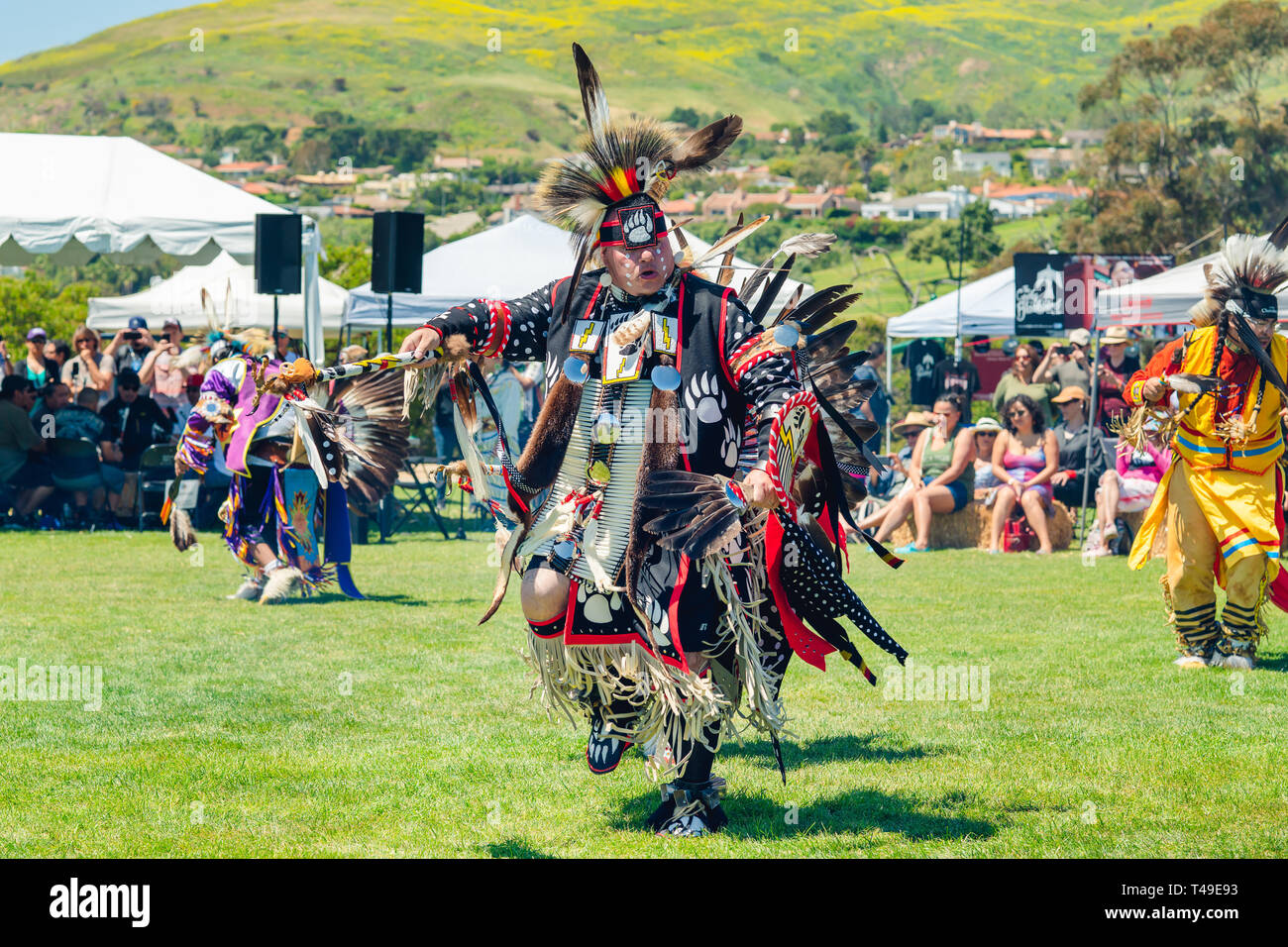 Several Native American dancers performs a dance to the drums at 2019 21st Annual Chumash Day Powwow and Intertribal Gathering, Malibu, California, Ap - Stock Image