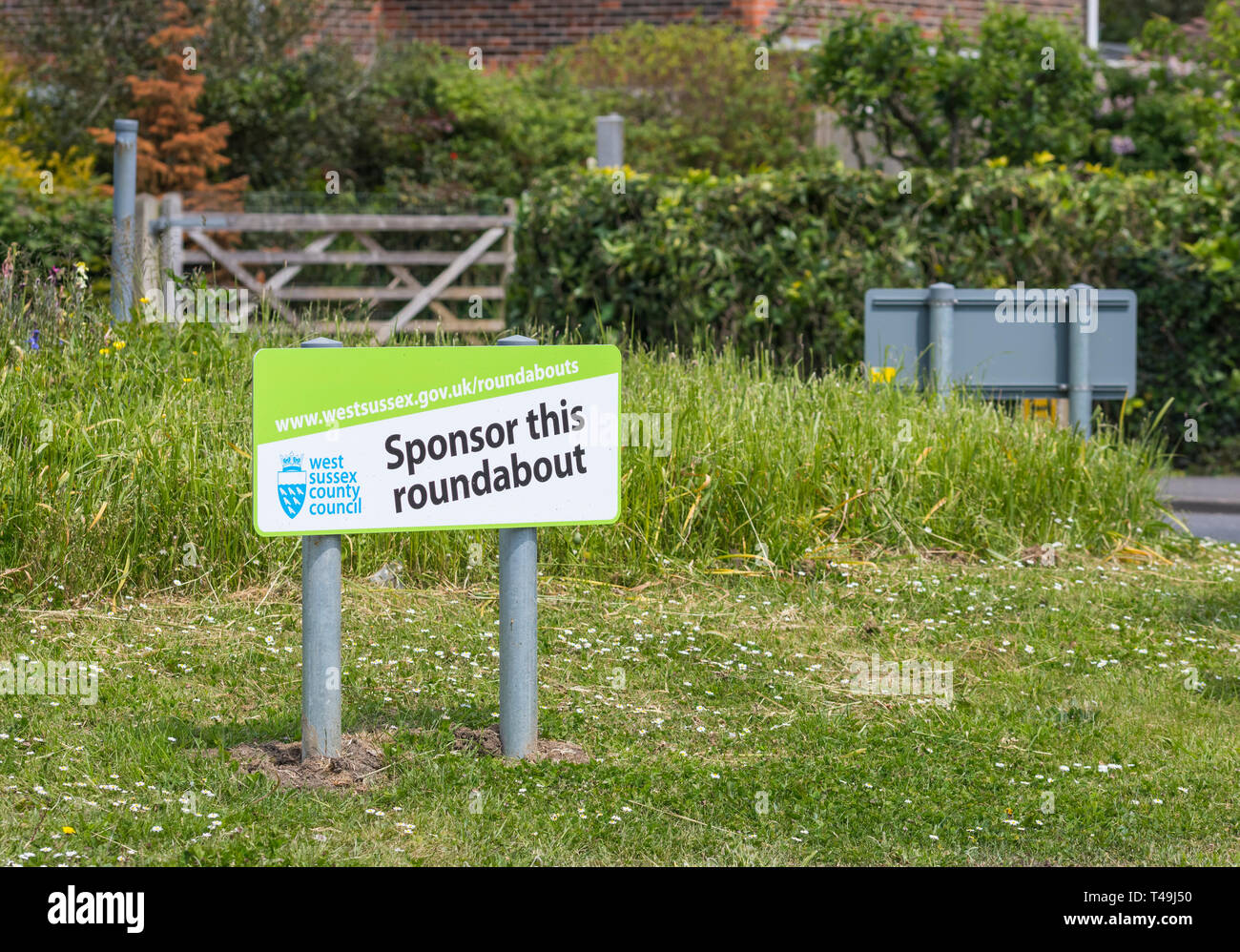 Sponsor this roundabout sign on a roundabout in the UK. - Stock Image