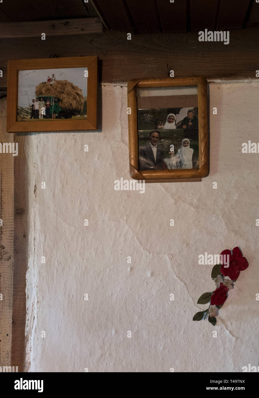 Lukomir, Bosnia. 9th July, 2018. Photos of a man's family hang on the wall. They have all left the village. In the mountains above Sarajevo at about 1500 meters lies Lukomir, the most remote village in all of Bosnia. The village consists mainly of nomadic sheep herder, adn a population of abotu 20 people. Being deemed unstrategic by the Serbs, Lukomir is one of the only areas that remained untouched during the war of the 1990's. The population of the village is slowly disappearing. With children leaving to attend school elsewhere and not coming back, what is the future of this village? Af - Stock Image