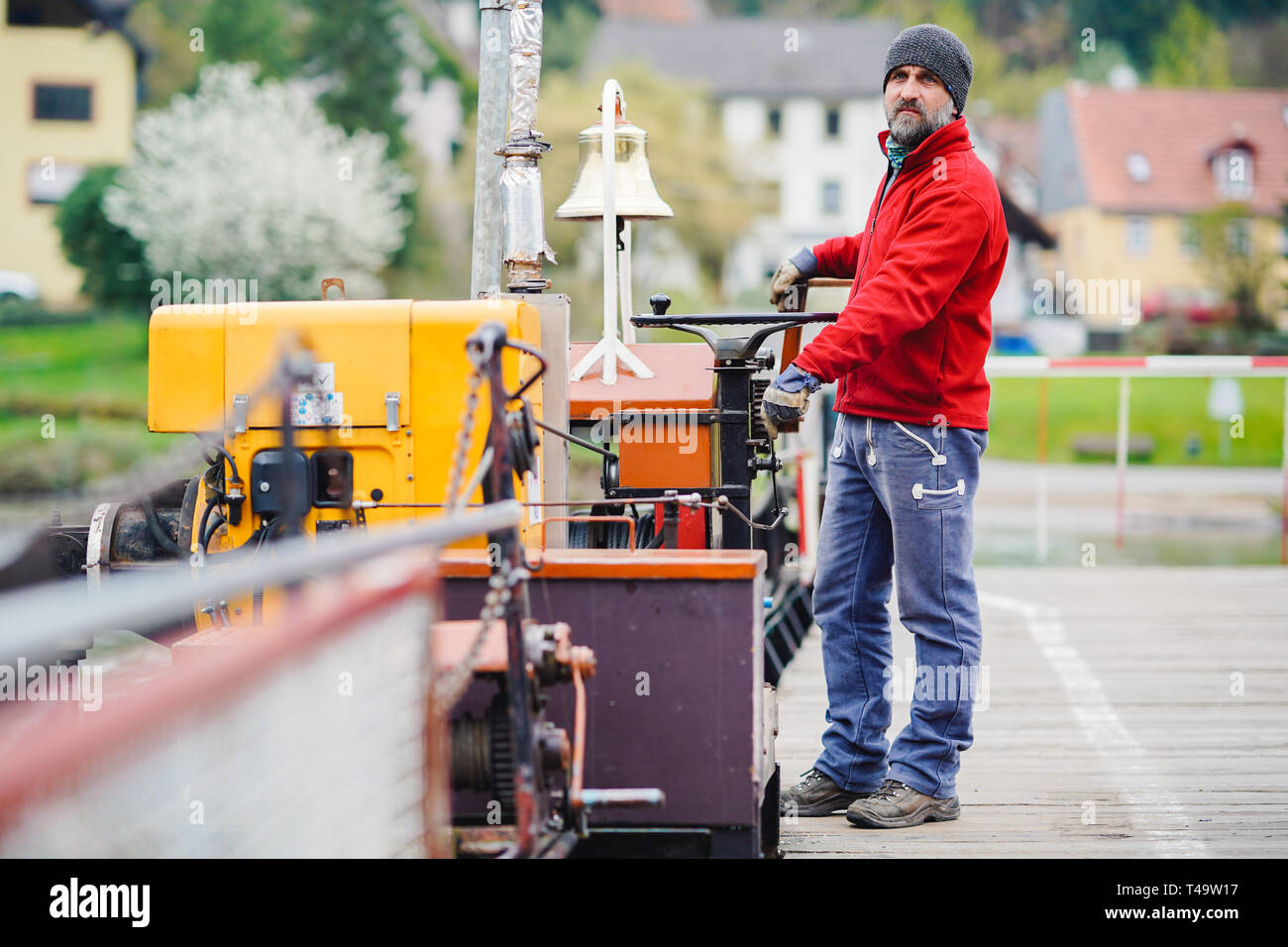 08 April 2019, Baden-Wuerttemberg, Neckargemünd: Ferryman Markus Seibert stands on the ferry across the Neckar between Neckarhausen and Neckarhäuserhof. (to dpa: 'Ferryman between the federal states - young talent worries solved' of 15.04.2019) Photo: Uwe Anspach/dpa - Stock Image