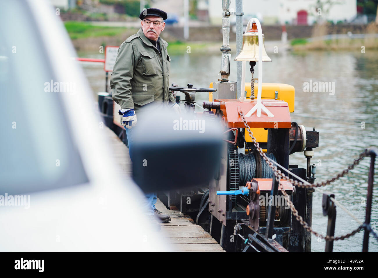 08 April 2019, Baden-Wuerttemberg, Neckargemünd: Ferryman Achim Landwehr stands on the ferry across the Neckar between Neckarhausen and Neckarhäuserhof. (to dpa: 'Ferryman between the federal states - young talent worries solved' of 15.04.2019) Photo: Uwe Anspach/dpa - Stock Image