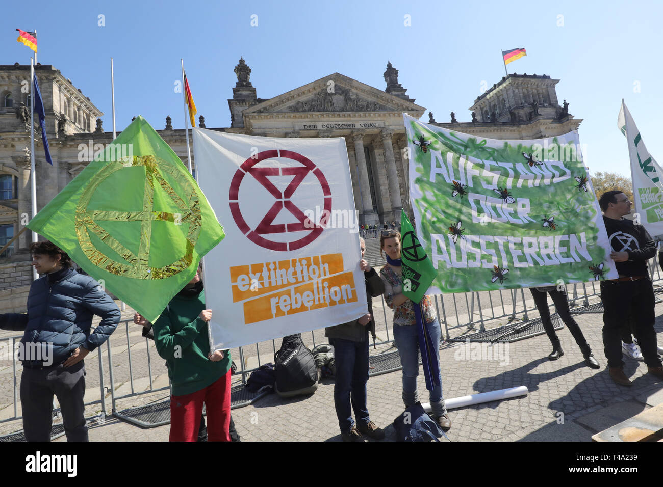 Berlin, Germany. 15th Apr, 2019. Participants of a rally of Extinction Rebellion Deutschland hold a banner with the inscription 'Aufstand oder Aussterben' in front of the Reichstag building. The movement wants to demonstrate between 15 and 27 April with several actions for climate protection. Credit: Wolfgang Kumm/dpa/Alamy Live News - Stock Image