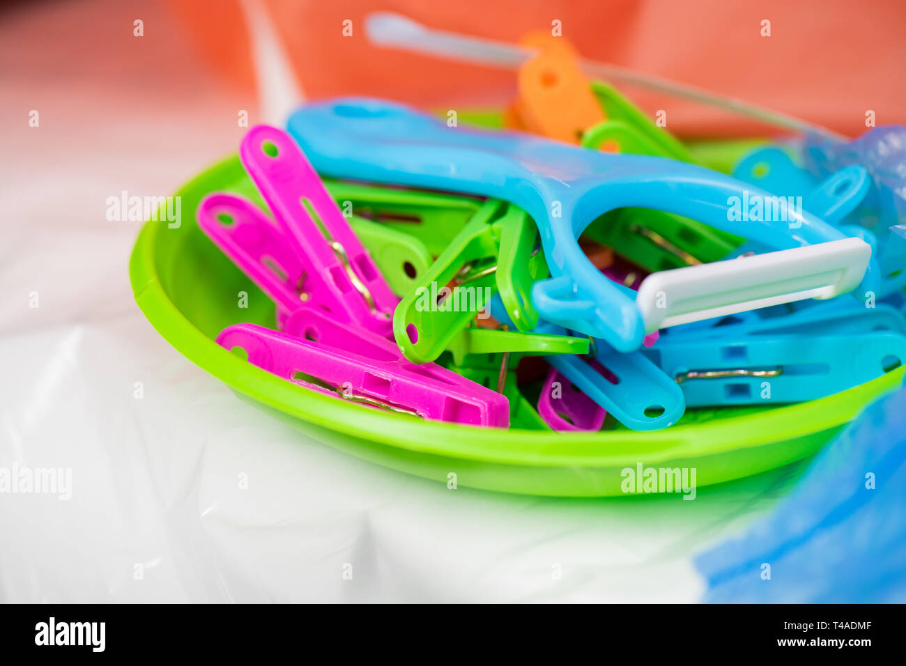 Useful tool made of harmful plastic being in pile with cheap pins - Stock Image