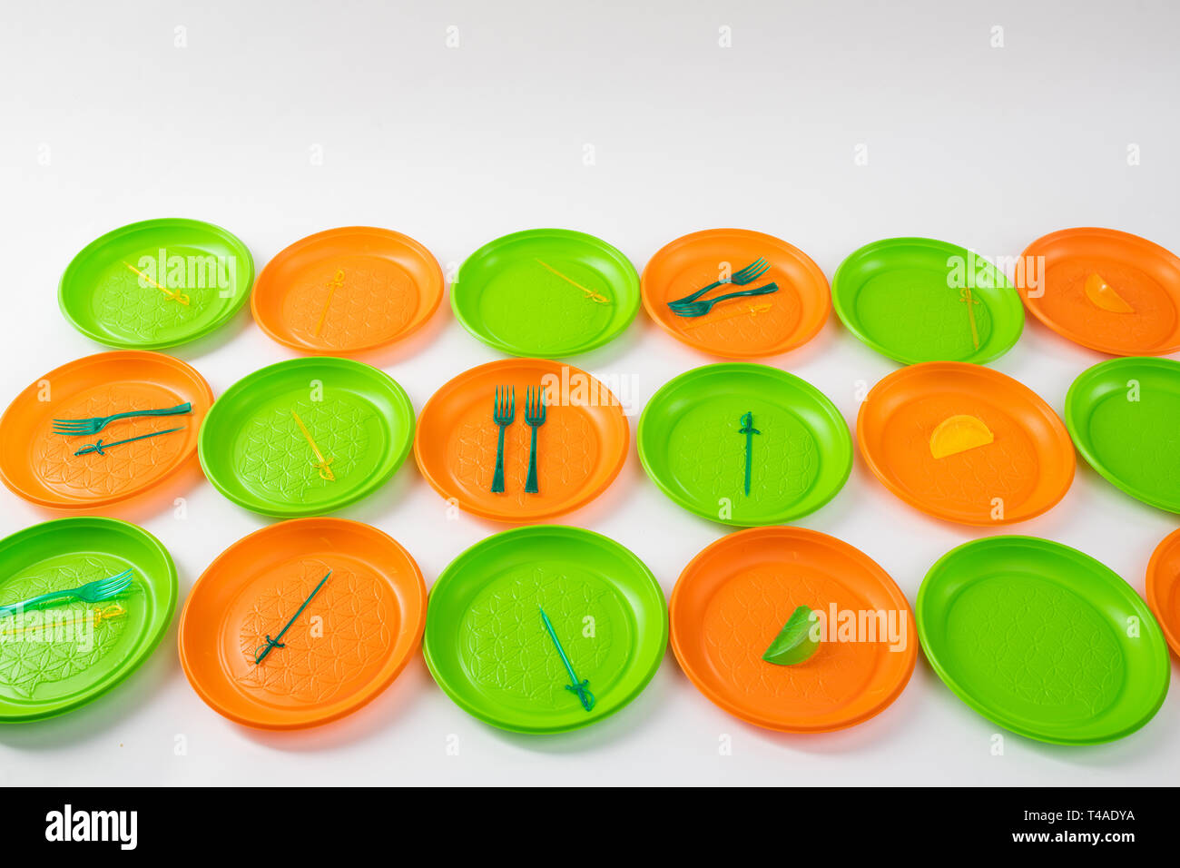 Colorful bright plastic plates setting apart and having forks and skewers - Stock Image