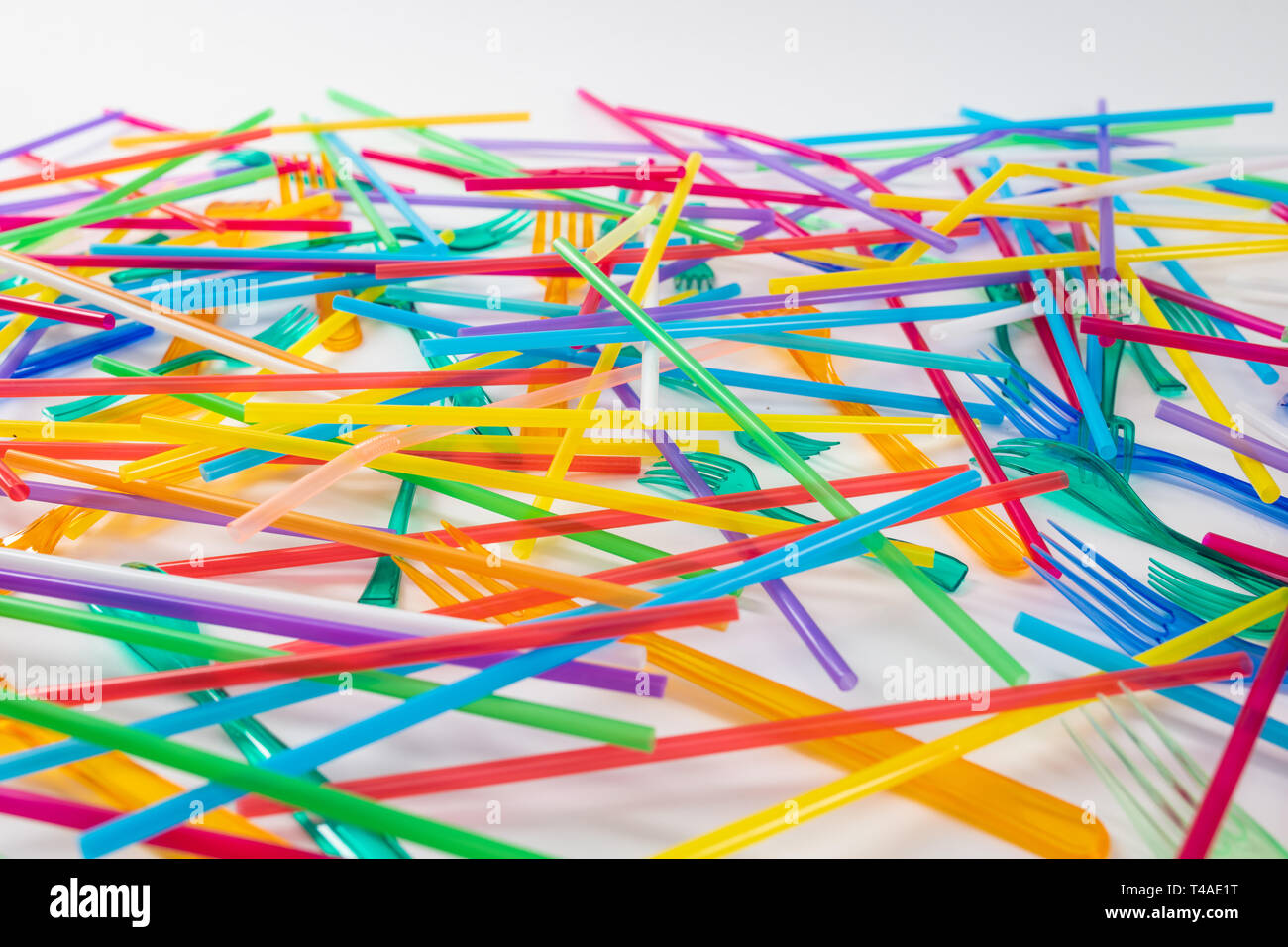 Bright and toxic disposable straws lying with colorful forks - Stock Image