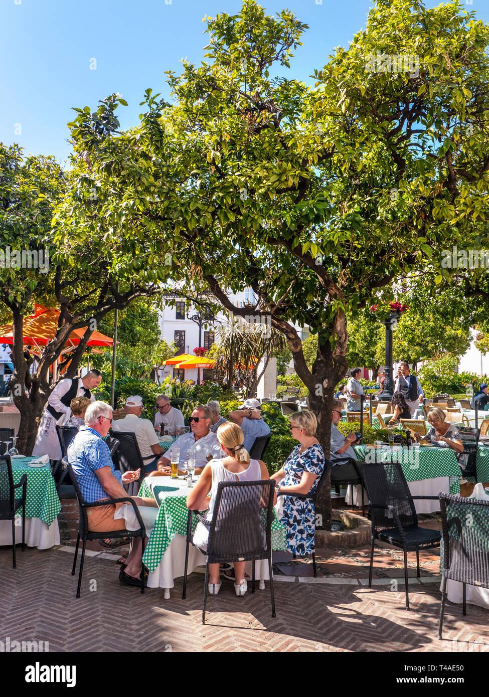 Alfresco dining Marbella Orange Square - Plaza de los Naranjos, Casco Antiguo. Outdoor dining, people enjoying food & wine in Old Town Marbella Spain - Stock Image