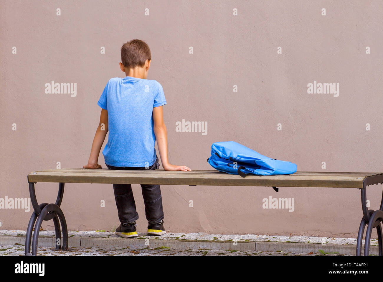 Sad alone child sitting on the bench outdoors. - Stock Image