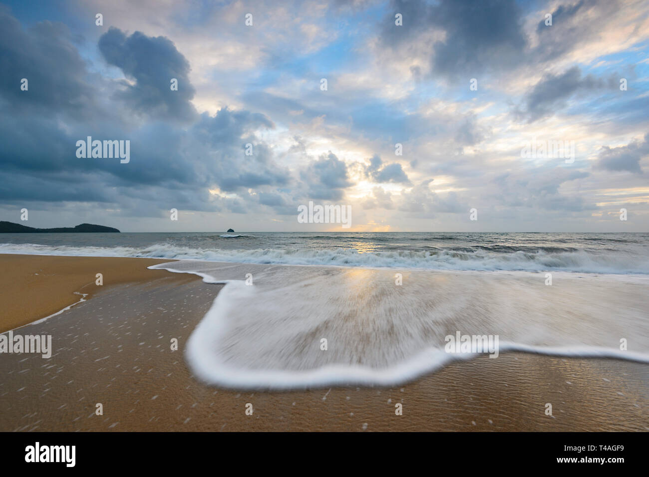 Stormy sky and gentle waves spume at sunrise, Palm Cove, Cairns Northern Beaches, Far North Queensland, FNQ, QLD, Australia - Stock Image