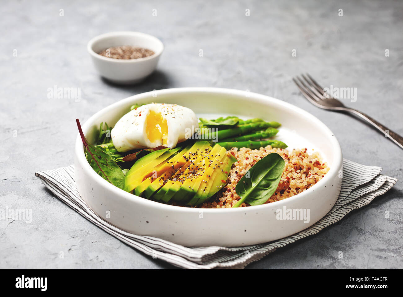 healthy breakfast. quinoa with egg, vegetables in a white plate on a gray background Stock Photo