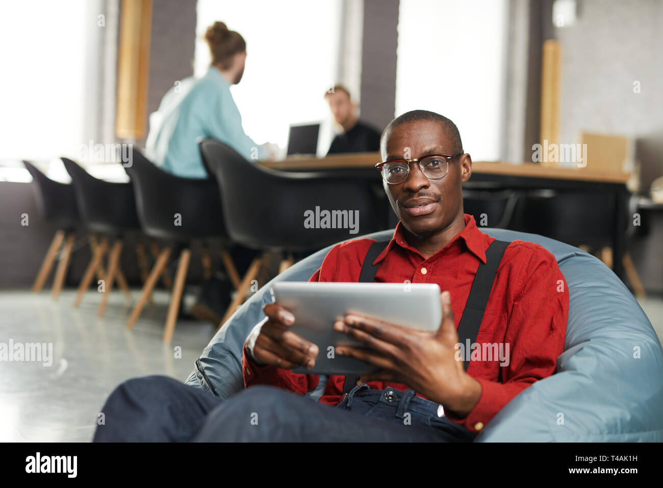 African -American Businessman Lounging in Office - Stock Image