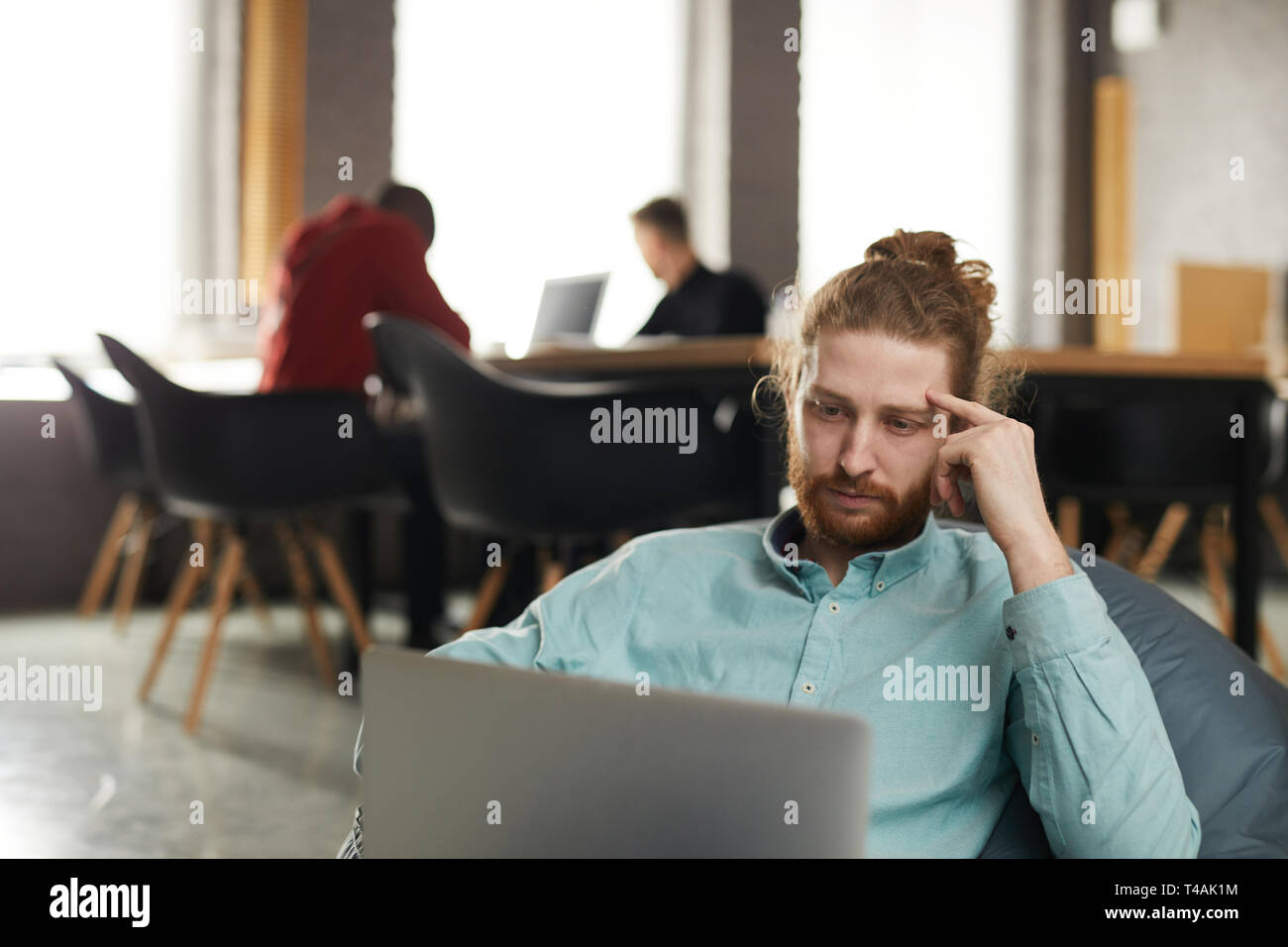 IT Specialist Working in Bean bag - Stock Image