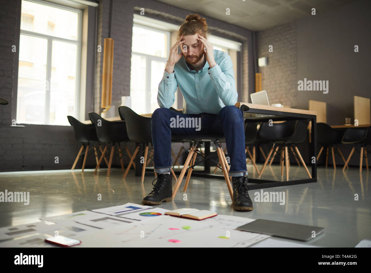 Puzzled Businessman Looking at Documents - Stock Image
