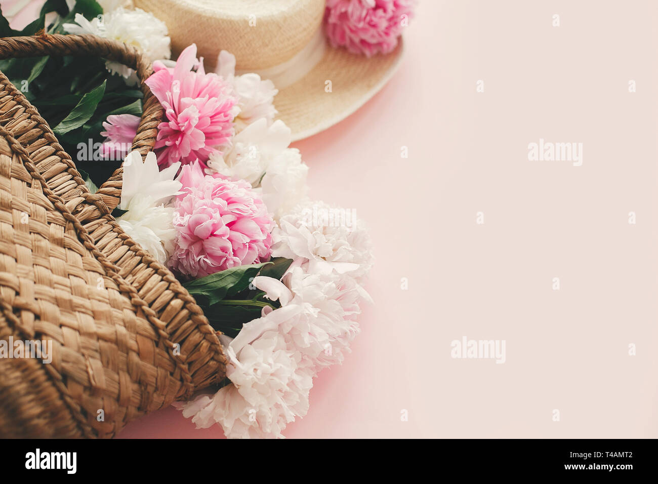 Stylish  straw rustic basket and hat with pink and white peonies on pink paper with space for text. Hello summer. International womens day. Happy moth - Stock Image
