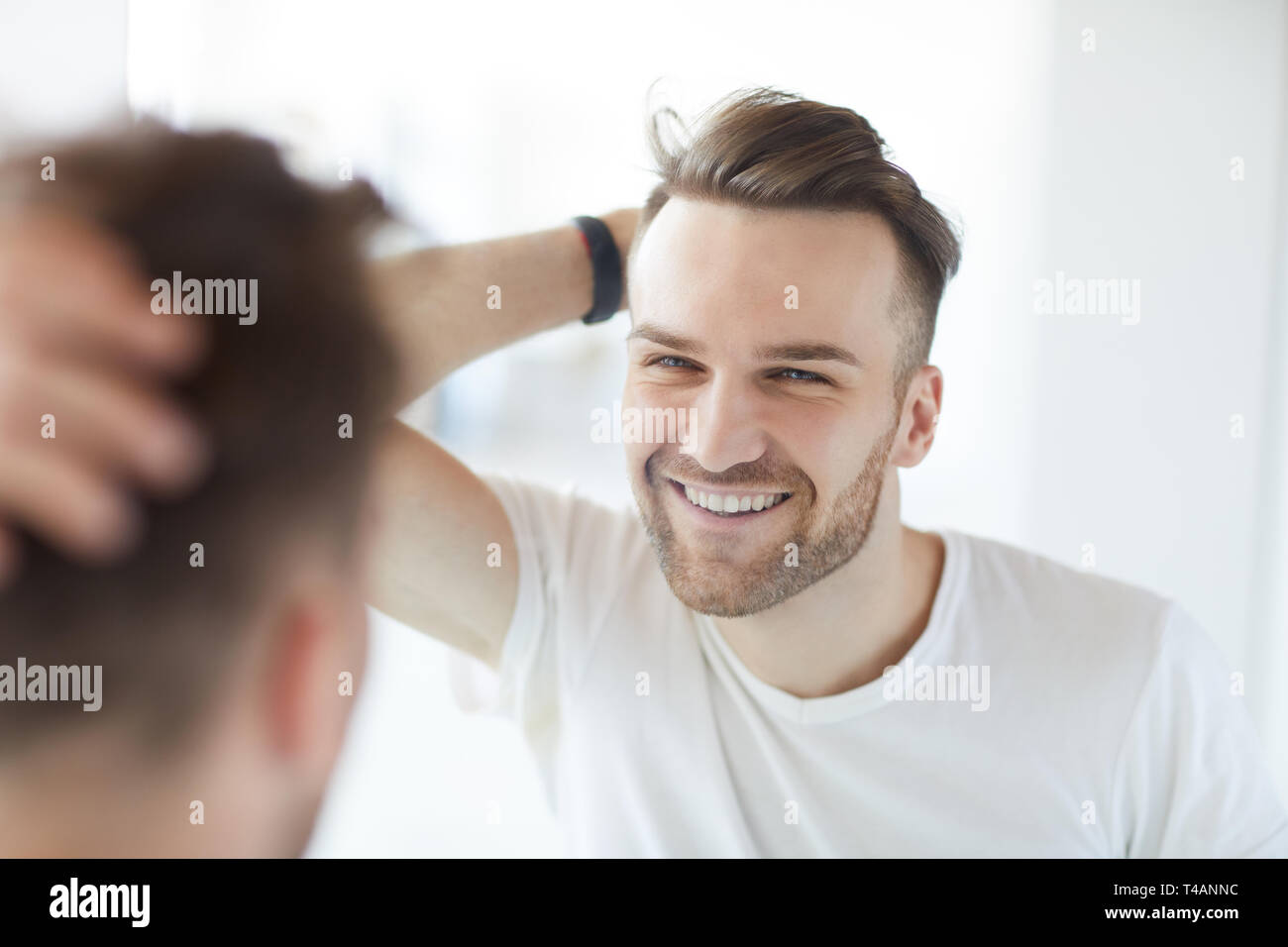 Handsome Man Looking in Mirror - Stock Image