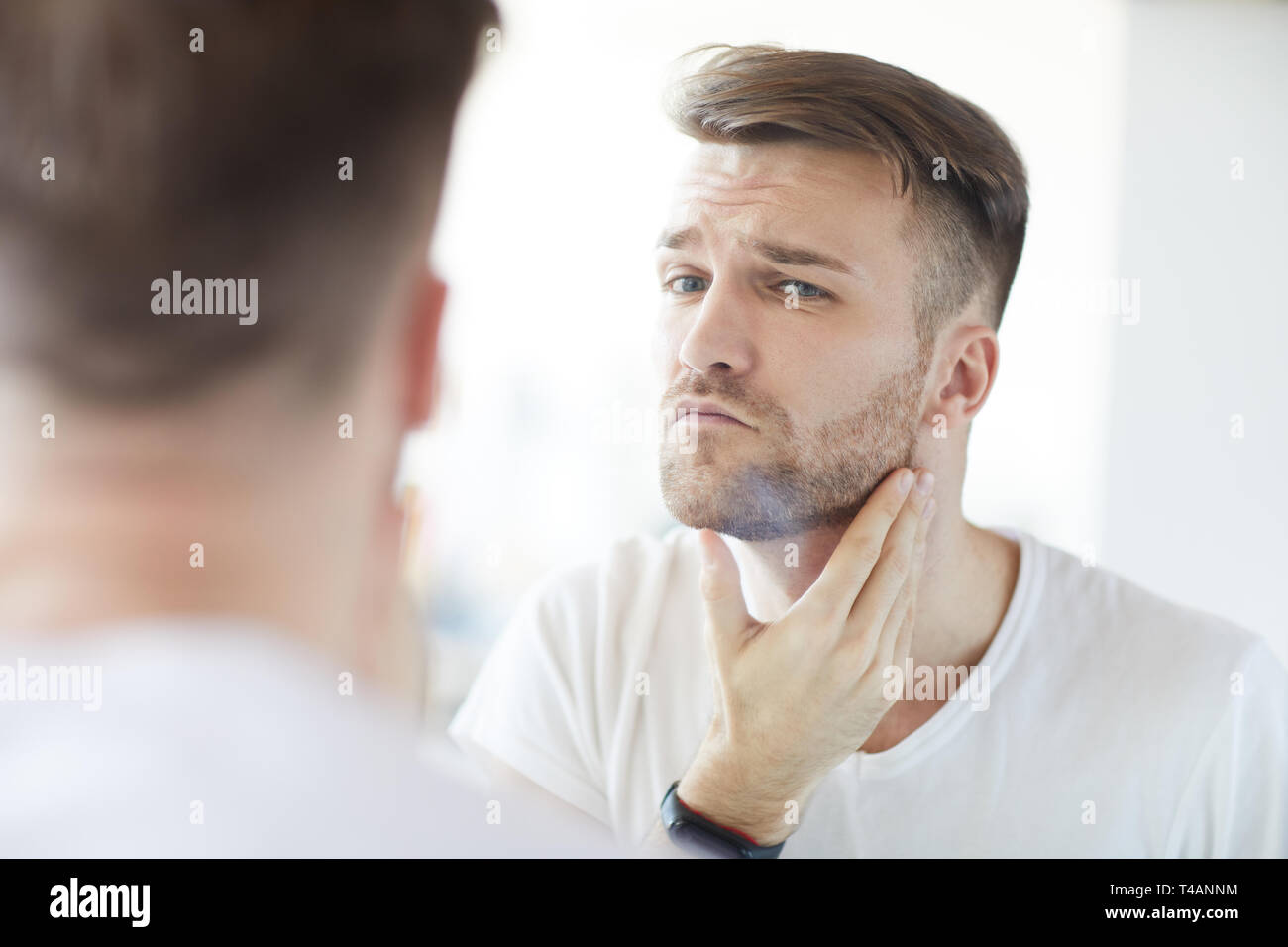Unshaved Man Looking in Mirror - Stock Image