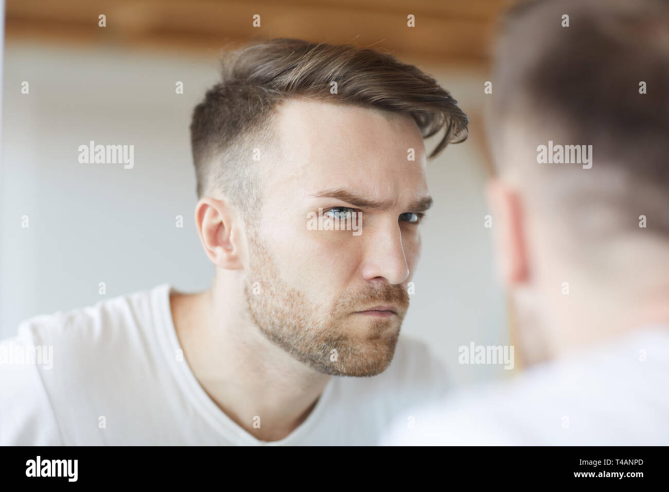 Frowning Man Looking in Mirror - Stock Image