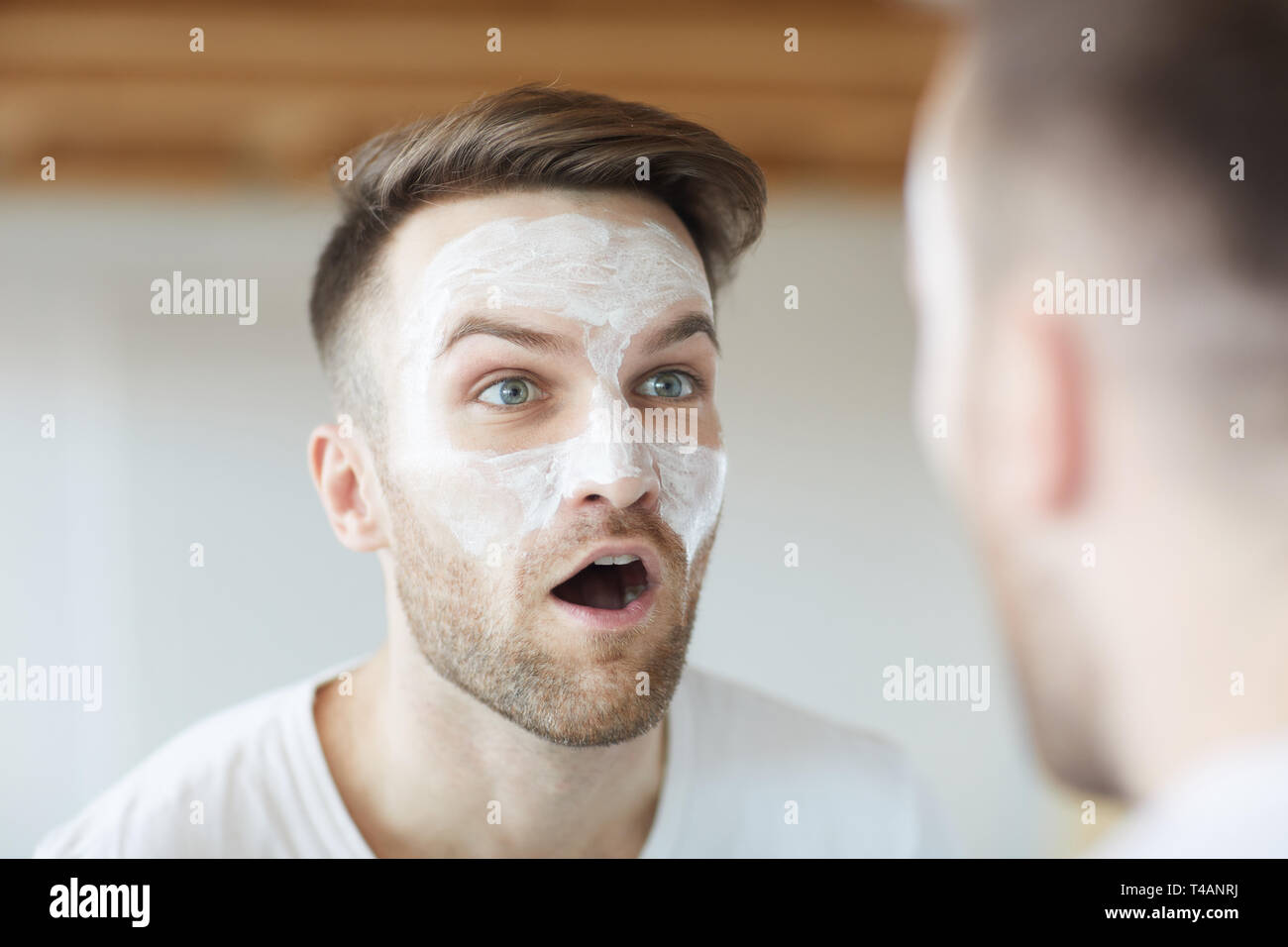 Man Making Faces at Mirror - Stock Image