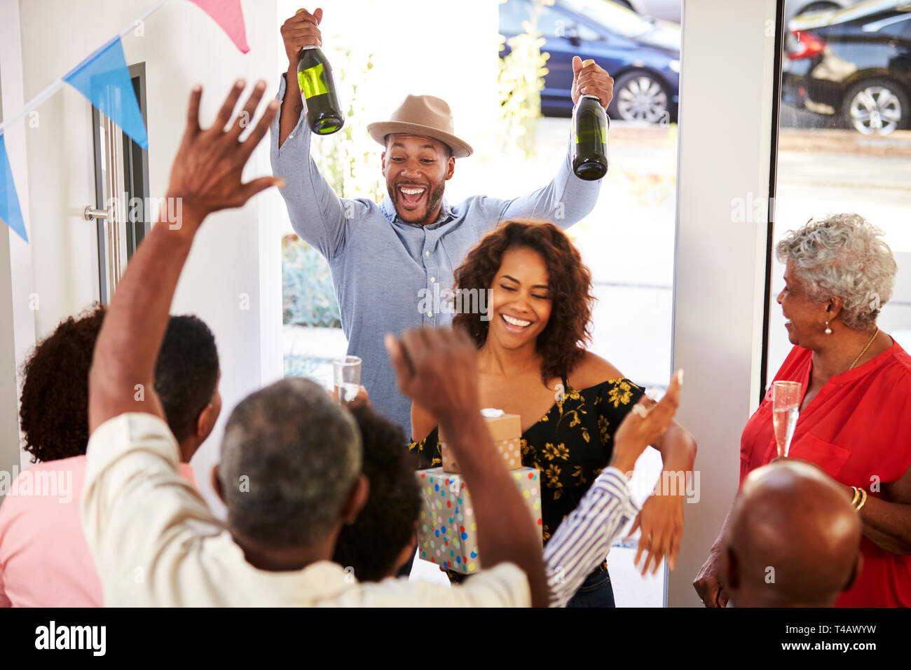 Three generation family throwing a surprise party welcoming guests at the front door,elevated view - Stock Image