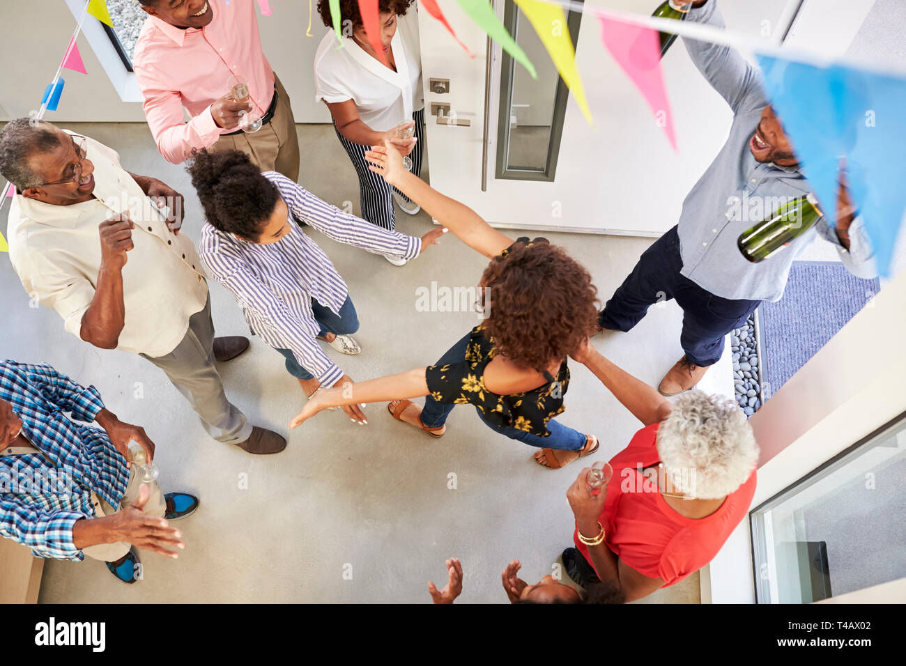 Three generation family throwing a surprise party welcoming guests at the front door,overhead view - Stock Image