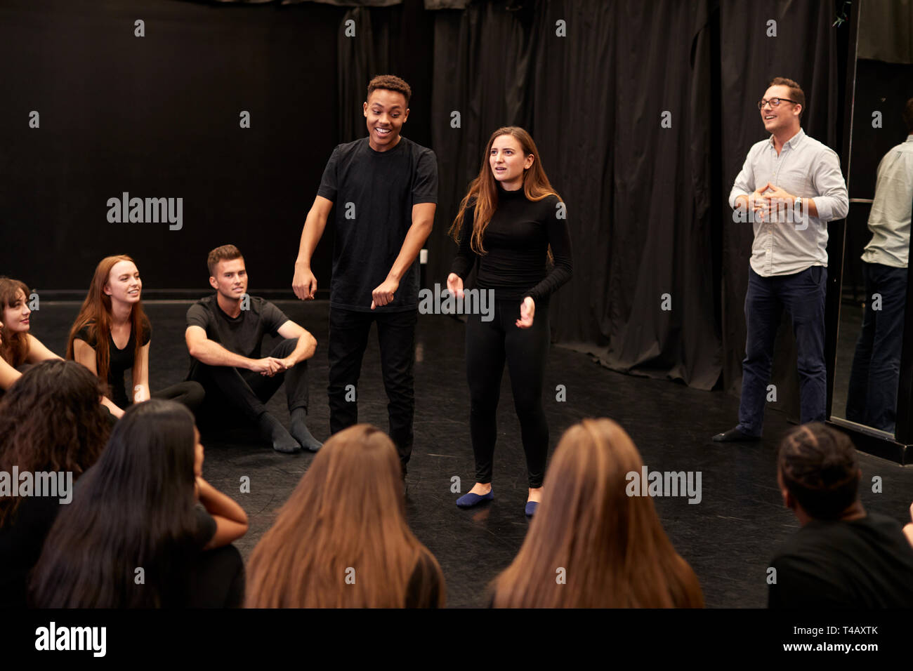 Teacher With Male And Female Drama Students At Performing Arts School In Studio Improvisation Class - Stock Image