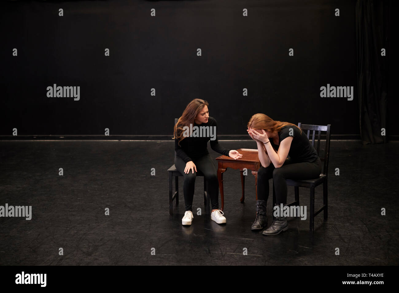 Two Female Drama Students At Performing Arts School In Studio Improvisation Class - Stock Image
