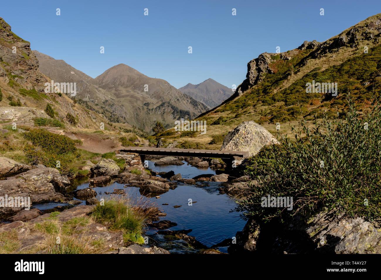 Wooden bridge in the hiking trail Estanys de Tristaina, Pyrenees, Andorra Stock Photo