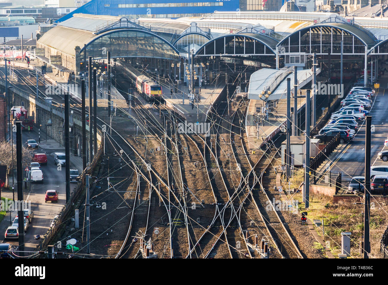 Grand old Newcastle Central railway station and multiple train tracks of the east coast main line and showing an express train at the platform - Stock Image