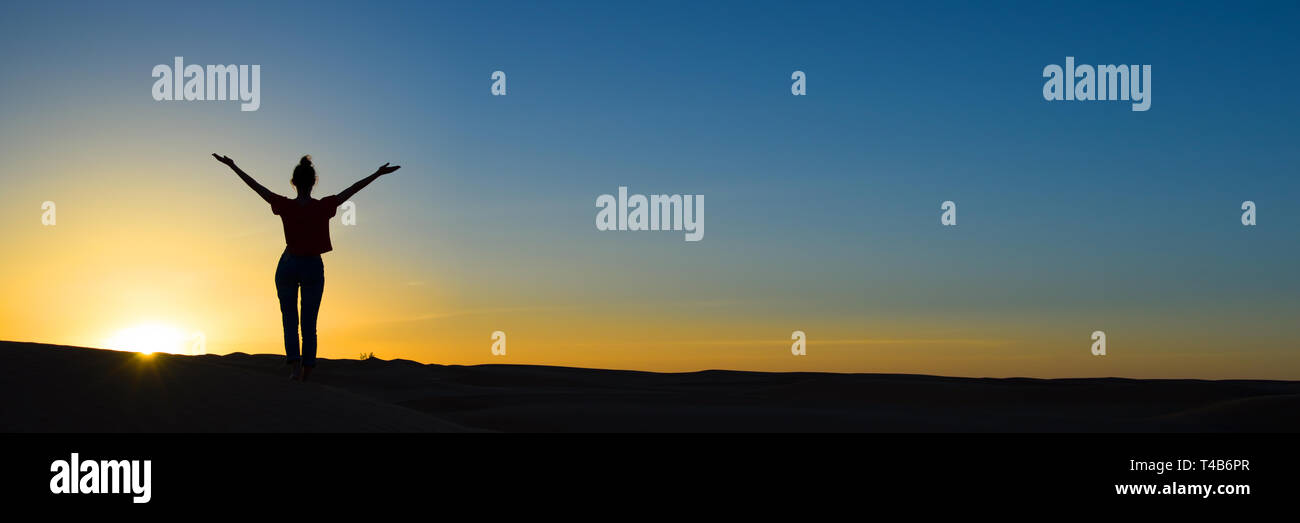 Silhouette of a woman standing in the sunset with the arms up, panoramic background with copy space - Stock Image