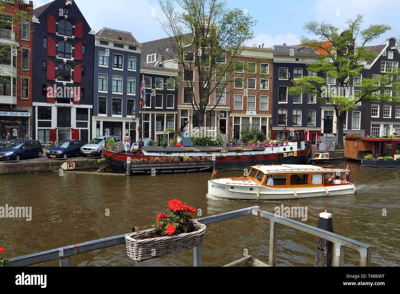 AMSTERDAM, NETHERLANDS - JULY 7, 2017: People visit Prinsengracht canal in Amsterdam, Netherlands. Amsterdam is the capital city of The Netherlands. - Stock Image