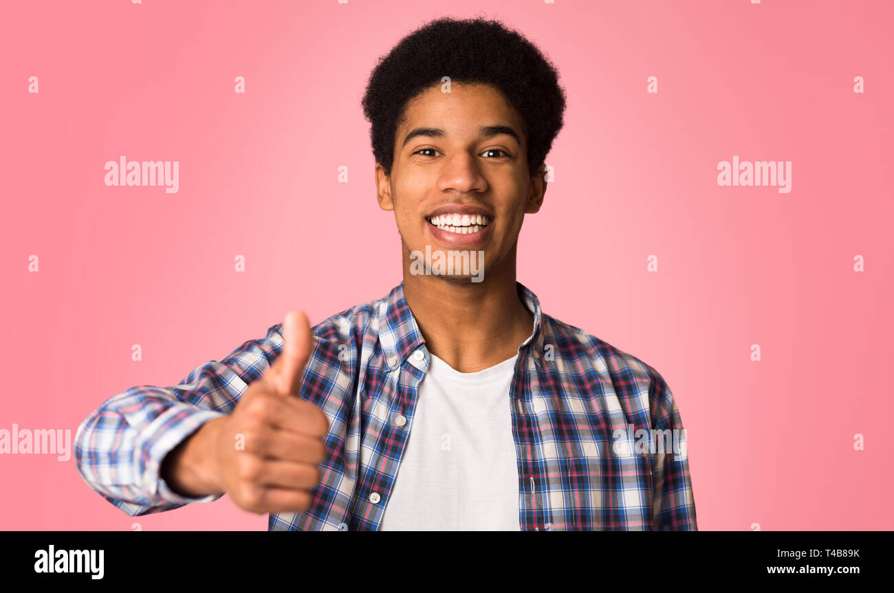 Recommend you. Happy guy showing thumb up and smiling - Stock Image