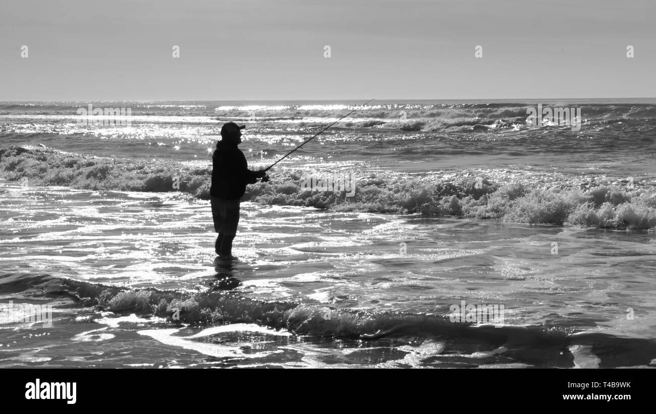 Silhouette of sport fisherman at the ocean wading in the water in black and white. - Stock Image