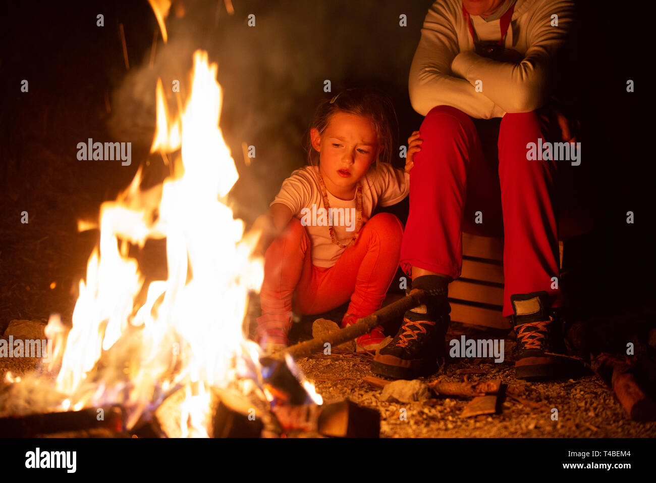 Mother and daughter spending quality time by a self-made campfire during adventurous camping trip, playing with fire. Active natural lifestyle, family - Stock Image