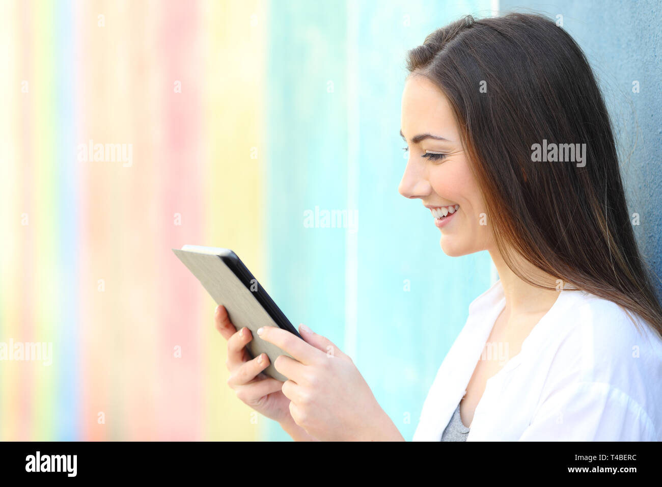 Side view pportrait of a happy girl on a colorful wall watching media on tablet - Stock Image