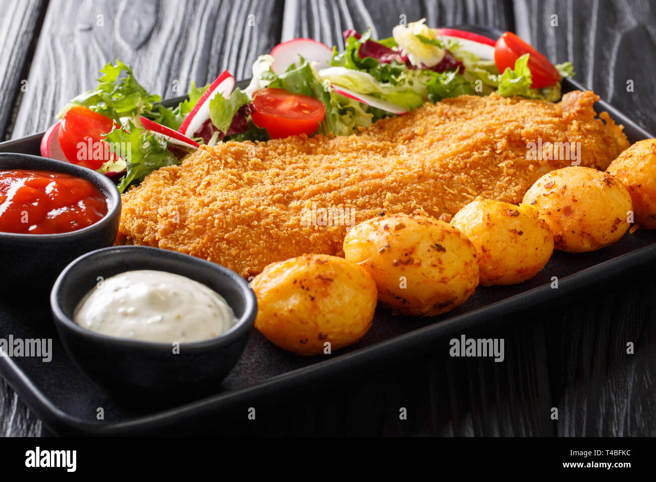 Served cod fillet in breading with new potatoes and fresh vegetable salad close-up on a plate on the table. horizontal - Stock Image