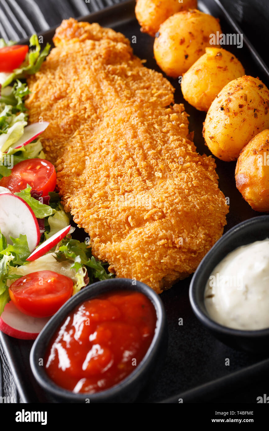 Cod fillet in breading with young potatoes and fresh vegetable salad close-up on a plate on the table. vertical - Stock Image